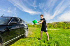 Man Washing Black Car in Green Field Stock Images
