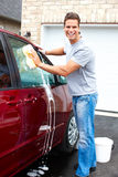 Man washing the car. Smiling happy man washing the red car Royalty Free Stock Images