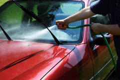 Man washing the car. With a water hose Stock Photography