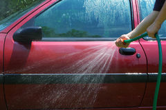 Man washing the car. With a water hose Stock Images