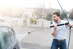 Man washing car in car wash station. Man washing his car in a self-service car wash station Royalty Free Stock Images