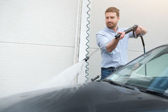 Man washing car in car wash station. Man washing his car in a self-service car wash station Stock Photo
