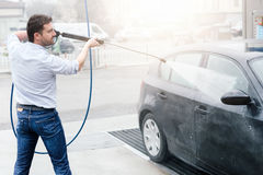 Man washing car in car wash station. Man washing his car in a self-service car wash station Stock Photography