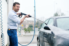 Man washing car in car wash station. Man washing his car in a self-service car wash station Royalty Free Stock Photography