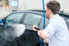 Man washing car in car wash station. Man washing his car in a self-service car wash station Royalty Free Stock Image