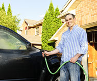 Man washing car on driveway. Man washing his car on the driveway stock image