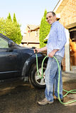 Man washing car on driveway. Man washing his car on the driveway royalty free stock images