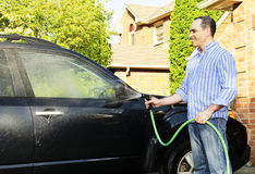 Man washing car on driveway. Man washing his car on the driveway royalty free stock photography