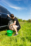 Man Washing Car in Field on Sunny Day Stock Photography