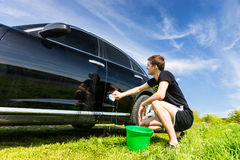 Man Washing Car in Field on Sunny Day Royalty Free Stock Images