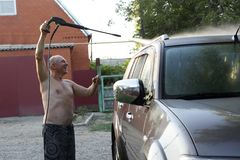 Man washing car. With high pressure washer Stock Photo