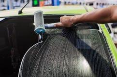A man washing a car's window using a rag Royalty Free Stock Photo