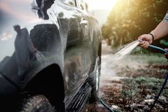 Man washing and cleaning car with spraying pressured water.  Stock Image