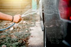 Man washing and cleaning car with spraying pressured water.  Stock Photo