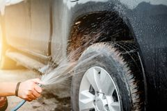Man washing and cleaning car with spraying pressured water.  Royalty Free Stock Photos