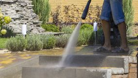 Man Washing Concrete Path With Pressure Washer. Close up royalty free stock images