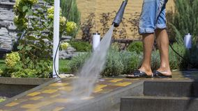 Man Washing Concrete Path With Pressure Washer. Close up stock photo