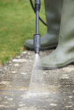 Man Washing Concrete Path With Pressure Washer. Man Washes Concrete Path With Pressure Washer royalty free stock photo
