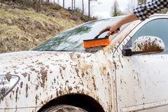 Man washing dirty car. Man washes away the dirt with a brush with a dirty car in the countryside Stock Image