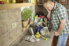Man washing dirty dishes in the kitchen sink. Domestic cleaning up after the party royalty free stock images