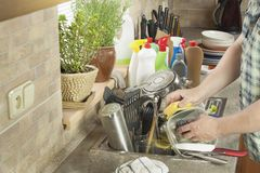 Man washing dirty dishes in the kitchen sink. Domestic cleaning up after the party royalty free stock photos