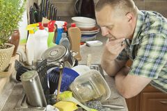 Man washing dirty dishes in the kitchen sink. Domestic cleaning up after the party royalty free stock image
