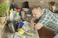 Man washing dirty dishes in the kitchen sink. Royalty Free Stock Images
