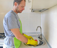 Man washing dish in the kitchen Stock Photos