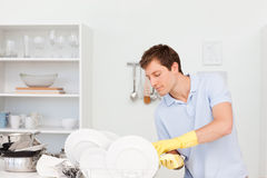 Man washing dishes Stock Images