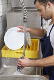 Man washing dishes. In a restaurant kitchen stock image