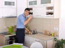 Man washing dishes. Happy young man washing the dishes after cooking Royalty Free Stock Photography