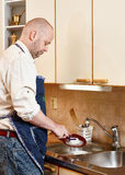 Man washing a dishes Royalty Free Stock Image
