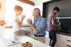 A man is washing dishes in the kitchen. The boy and the old man stand behind him and drink tea Stock Photos