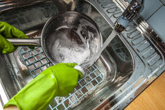 Man washing dishes in the sink. Man in green rubber gloves washing dishes in the sink under water Royalty Free Stock Photo