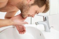 Man washing face in bathroom sink Stock Photos