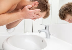 Man washing face in bathroom sink Royalty Free Stock Photography