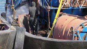 Man washing fishing trawler stock video footage