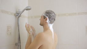 Man washing hair with shampoo in the shower. bathroom. stock video