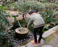 A man washing hands before coming to the temple in Tokyo, Japan Stock Images