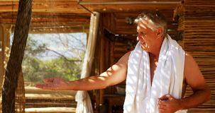 Man washing hands from shower in cottage during safari vacation 4k. Smiling man washing hands from shower in cottage during safari vacation 4k stock footage
