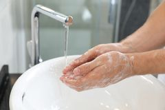 Man washing hands with soap over sink. In bathroom, closeup royalty free stock image