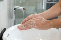 Man washing hands with soap over sink in bathroom. Closeup royalty free stock photography