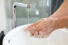 Man washing hands with soap over sink in bathroom. Closeup stock photos