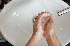 Man washing hands with soap over sink in bathroom. Top view. Space for text royalty free stock image