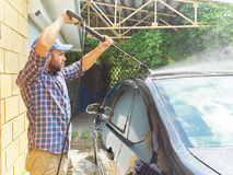 Man washing his black car near house. Stock Images
