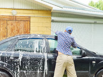Man washing his black car near house. Royalty Free Stock Image