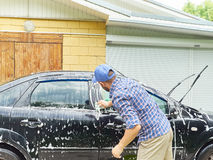 Man washing his black car near house. Stock Image
