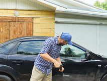 Man washing his black car near house. Stock Photography