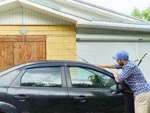 Man washing his black car near house. Stock Photo