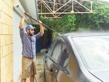 Man washing his black car near house. Royalty Free Stock Images